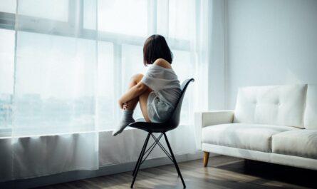 Dívka sedí osamocena v pokoji, protože má deprese.