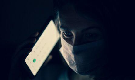 Muže má u obličeje telefon s aplikací eRouška.