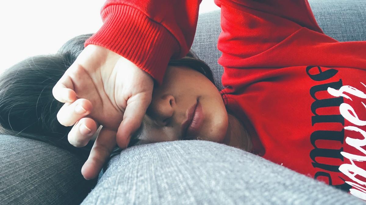 Dívka leží na pohovce, protože má únavový syndrom.